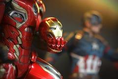 Близкая поднимающая вверх маска съемки в руке Ironman в диаграмме superheros МСТИТЕЛЕЙ в действии стоковое фото