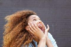 Близкая поднимающая вверх молодая женщина с удивленным выражением и смотреть стороны вверх стоковые фото