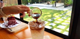 Близкая поднимающая вверх рука людей лить не доходя темного кофе эспрессо в стекле соды льда стоковые фото
