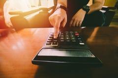 Близкая поднимающая вверх рука человека используя калькулятор высчитывая bonusOr другая компенсация к работникам для увеличения у стоковые фотографии rf