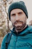 Близкая поднимающая вверх съемка голубого наблюданного человека имеет темную щетинку, смотрит серьезно на камере, носит шляпу и к стоковое фото rf