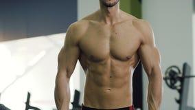 Близкая поднимающая вверх съемка мужского торса во время нагнетая мышцы оружий делая тренировки со штангами в спортзале видеоматериал