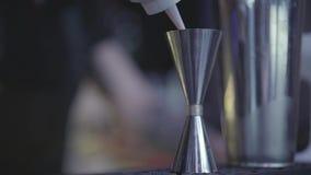 Близкая поднимающая вверх съемка напитка руки бармена лить от бутылки в измеряя чашку акции видеоматериалы