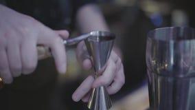 Близкая поднимающая вверх съемка напитка руки бармена лить от измеряя чашки в шейкер металла видеоматериал