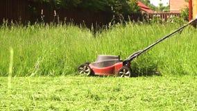 Близкая поднимающая вверх съемка резать траву с электрической газонокосилкой сток-видео