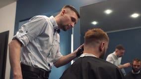Близкая поднимающая вверх съемка человека получая ультрамодную стрижку на парикмахерской Мужской клиент сервировки парикмахера, д сток-видео