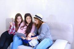 Близкие женские друзья используют таблетку и имеют потеху, сидят на кресле в ro Стоковая Фотография RF