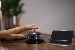 Близкие поднимающие вверх женщины вызывают прием гостиницы на встречном столе с пальцем для нажатия колокола в гостинице лобби ко стоковые фотографии rf