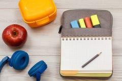близкие поставкы школы транспортира компаса вверх Наушники, яблоко, желтая коробка для завтрака и открытое бывшее Стоковые Фотографии RF