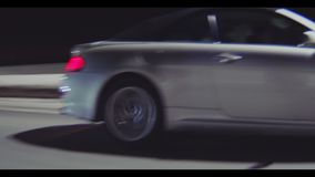 Близкий автомобиль спорт управляет вдоль улицы за светами в вечере акции видеоматериалы