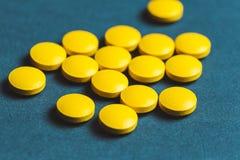 близкий вверх желтых таблеток на голубой предпосылке стоковые фото