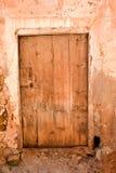близкий вверх старой деревянной закрытой двери в стене бетона, грязи и камня в закрытом получившемся отказ доме где никто живет стоковая фотография rf