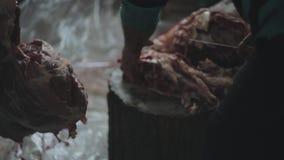 Близкий взгляд мужского вырезывания большая часть сырого мяса в части с ножом 2 других люд помогают ему только сток-видео