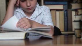 Близкий мальчик сидит за столом. читает книгу, скучает по страницам сток-видео