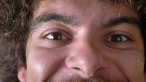 Близкий отснятый видеоматериал шального человека наблюдает смотрящ камеру и усмехающся, вьющиеся волосы с томом акции видеоматериалы