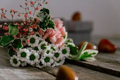 Близкий поднимающий вверх букет цветка с подарочной коробкой и камень на деревянной предпосылке Смогите быть использовано для сва стоковое фото