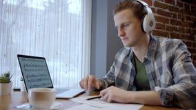 Близкий поднимающий вверх взгляд молодых пианиста или гитариста пробуя составить его новую песню в дезертированном перерыве на ча акции видеоматериалы
