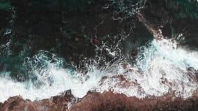 Близкий поднимающий вверх взгляд сверху огромного бурного рему волн в скалы, создавая белую пену и брызгать сток-видео