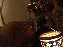 Близкий поднимающий вверх взгляд феи сидя на carousel вращения свечи металла луны с формами звезд осветил, перед открытой книгой, стоковое фото rf