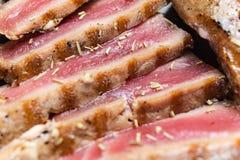 Близкий поднимающий вверх натюрморт стейков тунца Roasted Crusted с травами и семенами сезама на темном - серая поверхность стоковые изображения rf