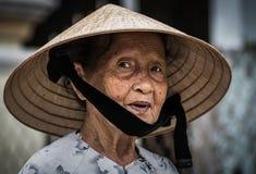 Близкий поднимающий вверх портрет въетнамской старухи нося традиционную коническую шляпу стоковое фото