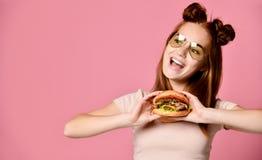 Близкий поднимающий вверх портрет голодной молодой женщины есть бургер изолированный над белой предпосылкой стоковые фото