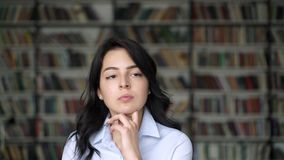 Близкий поднимающий вверх портрет думая девушки на предпосылке полок библиотеки видеоматериал