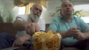 Близкий поднимающий вверх портрет 2 зрелых старших людей смотря ТВ дома Друзья наблюдая футбол футбола пока ел обломоки сток-видео