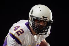 Близкий поднимающий вверх портрет игрока спортсмена американского футбола в действии на черной предпосылке изолированная принципи стоковая фотография rf