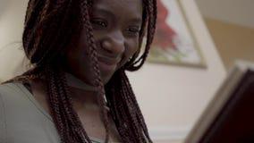 Близкий поднимающий вверх портрет красивой американской африканской женщины смотря фотоальбом с интересными и смешными photoes в  акции видеоматериалы