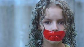 Близкий поднимающий вверх портрет курчавой грустной девушки подростка с ее ртом связанным тесьмой сверх с бюрократизмом Нарушение акции видеоматериалы