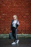 Близкий поднимающий вверх портрет меньшей красивой стильной девушки ребенк около красной кирпичной стены как предпосылка стоковые изображения