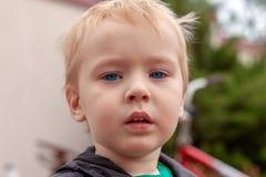 Близкий поднимающий вверх портрет милого кавказского ребенка с серьезным выражением в голубых глазах справедливые волосы взволнов стоковые фотографии rf