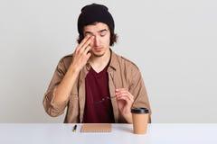 Близкий поднимающий вверх портрет молодого небритого мужчины с волнистыми волосами, сидя на столе, имеет боль в глазах, принимает стоковая фотография rf