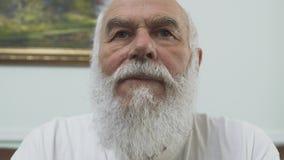Близкий поднимающий вверх портрет старшего зрелого старого бородатого человека сидя на кожаном диване дома есть обломоки закрывае сток-видео
