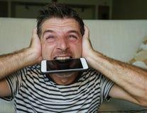 Близкий поднимающий вверх портрет стороны молодого привлекательного и усиленного мобильного телефона человека сдерживая отчаянног стоковые изображения rf