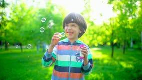 Близкий поднимающий вверх портрет счастливого маленького милого мальчика дуя, имеющ потеху с пузырями мыла в парке Маленький ребе сток-видео