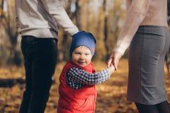 Близкий поднимающий вверх портрет счастливого мальчика в голубой крышке держа его руки родителей на открытом воздухе в парке стоковая фотография