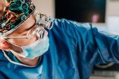 Близкий поднимающий вверх портрет хирурга выполняя хирургию на пациенте в операционной больницы стоковые изображения