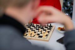 Близкий поднимающий вверх человек обдумывает его следующий шаг играя шахматы стоковые фотографии rf