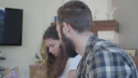 Близкий поднимающий вверх человек портрета в рубашке шотландки и милой женщине пакуя их ткань к большим чемоданам Концепция подго видеоматериал