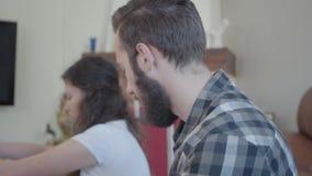Близкий поднимающий вверх человек портрета в рубашке шотландки и милой женщине пакуя их ткань к большим чемоданам Концепция подго акции видеоматериалы