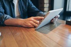 Близкий поднимающий вверх человек рук используя планшет, соединяясь wifi Работа как раз от кафа стоковые фото
