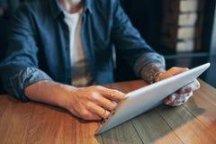 Близкий поднимающий вверх человек рук используя планшет, соединяясь wifi Работа как раз от кафа стоковое изображение