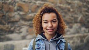 Близкий портрет Афро-американской девушки при светлое вьющиеся волосы нося вскользь одежду смотря камеру и усмехаться сток-видео