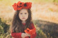 Близкий портрет девушки маленького ребенка при большой коричневый цвет щек наблюдает и губы pout нося стильное красное платье с м Стоковые Изображения
