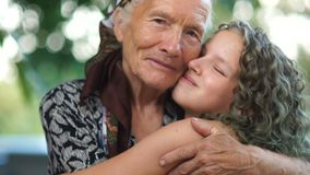 Близкий портрет обнимать бабушки и внучки Пожилая женщина в головном платке и девушка подростка с покрашенный сток-видео