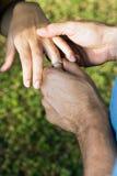близкий человек перста o кладет кольцо s вверх по вертикальной женщине Стоковая Фотография