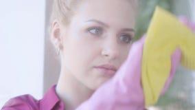 Близкое лицо усталой блондинки, моющей окно с тряпкой окна в комнате Домашнее хозяйство акции видеоматериалы
