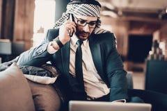 Близкое поднимающее вверх фото арабский говорить по телефону на кресле стоковая фотография rf